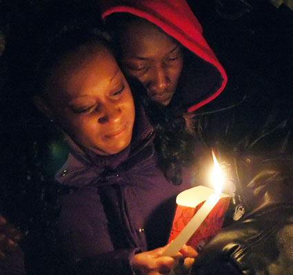 Sandra Campbell holds a lighted candle during vigil