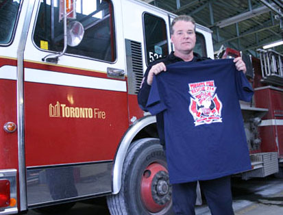 Rob Bygrave, Captain of Station 214 holds up a t-shirt emblazoned with the fire station's crest.