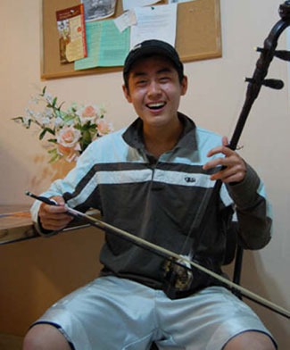 Nan Li, a young Erhu performer is playing the Erhu in his home in Scarborough.
