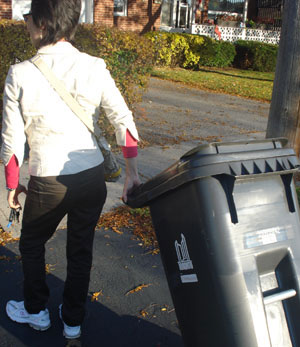 A homeowner takes in her grey bin. These new garbage bins have posed some challenges for people.