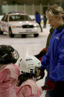 Police Constable Terry Lynn gives two first-time skaters a helping hand during Family Skate Day at Heron Park Arena. (Matthew Alleyne/Toronto Observer)